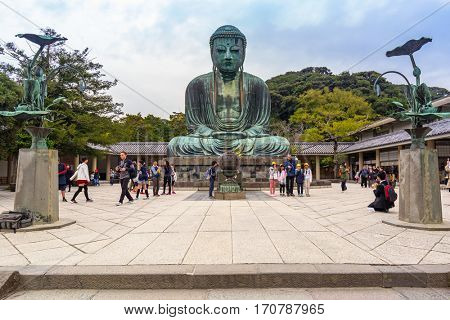 KAMAKURA, JAPAN - NOVEMBER 8, 2016: Tourists at statue of The Great Buddha of Kamakura, Japan. Monumental outdoor bronze statue of Amida Buddha is one of the most famous icons in Japan.