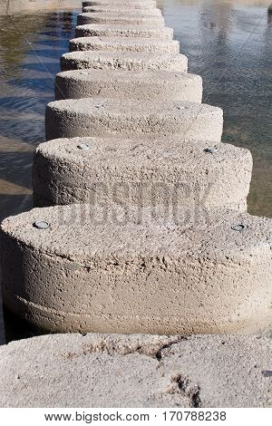 Vertical image with stepping stones leading upwards through water.