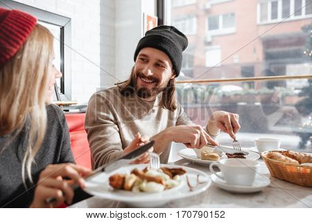 Side view of attractive couple sitting by the table and eating in cafe. As well as couple looking to each other