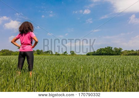 Rear view of young woman girl female runner jogger hands on hips standing in green field with blue sky