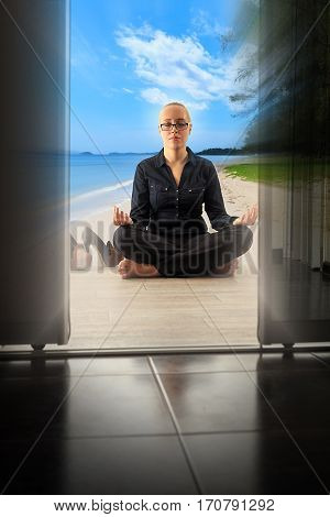Young woman doing yoga at the office sand and sea on the floor and clouds in the sky tropical nature at background concept of stress and relaxation