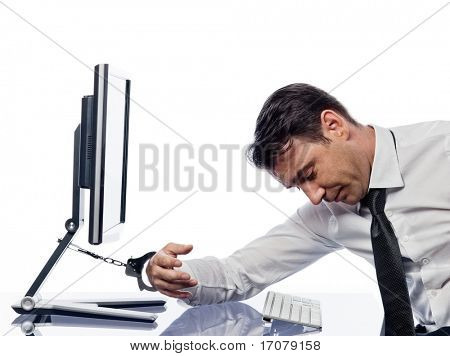 caucasian man chained to computer with handcuffs expressing slavery to computer concept isolated studio on white background