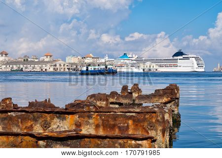 Beautiful view of the bay of Havana in Cuba with old buildings and cruiser ships and a rusty iron pier on the foreground