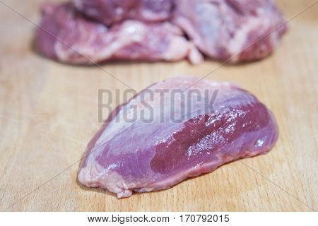 Raw meat cheek pieces of iberian pork over wooden board. Isolated over white background
