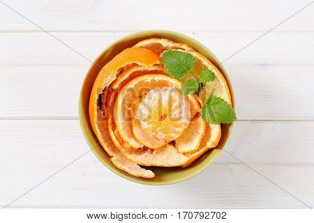 peeled orange arranged in peels in green bowl