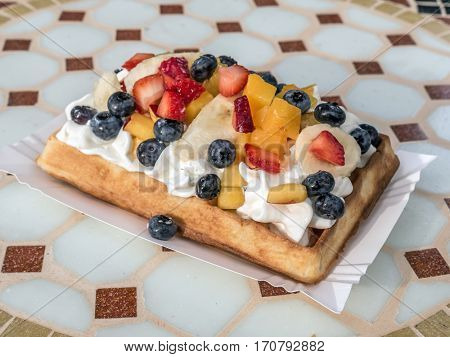 Crisp waffle with whipped cream and liquid chocolate served on coffee table