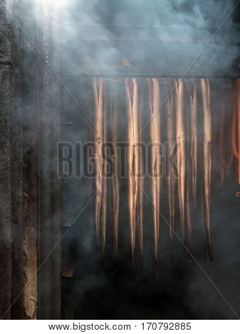 Fresh marine fish being smoded in smokehouse