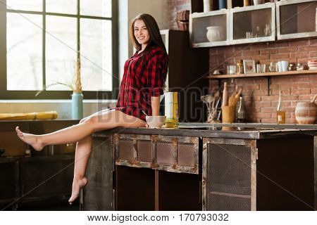 Full length young beauty woman in red shirt with naked legs sitting on the table and looking at camera in kitchen. Side view