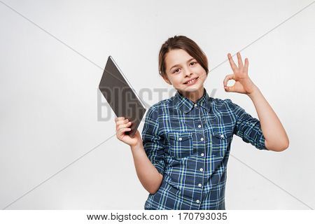 Picture of cheerful young girl using tablet computer make okay gesture isolated over white background.