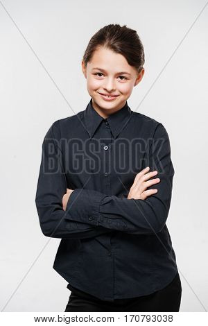 Picture of attractive young girl posing with arms crossed isolated over white background.