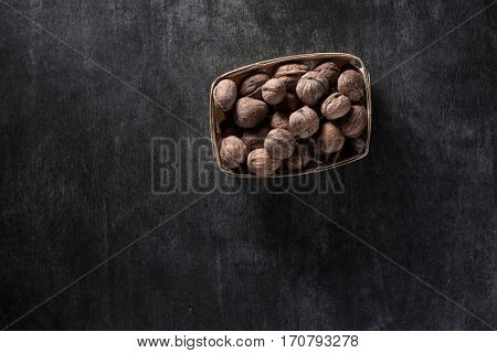Top view picture of a lot of walnuts over dark background