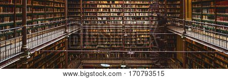 AMSTERDAM, NETHERLANDS - January 28, 2017: Panoramic view inside great public library with many books - The Rijksmuseum Library, Amsterdam, Netherlands
