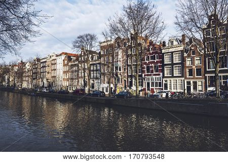 AMSTERDAM, NETHERLANDS - January 28, 2017: Tradition colorful Amsterdam houses across canal with bare trees, bikes and cars parked in front of them and cloudy sky background