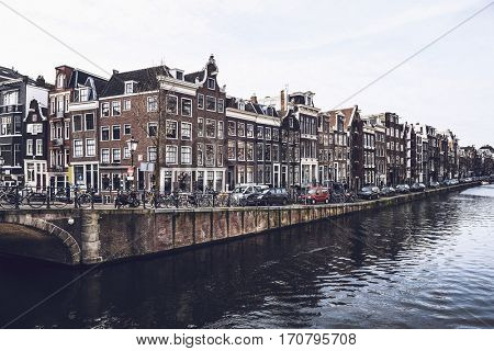 Beautiful historical houses and cars parked on street next to water of canal in Amsterdam, Netherlands