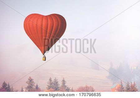Red air balloon in shape of heart fly above forest in foggy morning. Romantic postcard background on Valentine's Day. Adventure trip for couples. Sport and recreation travel theme. Nature background