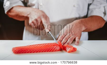 Chef coock dressed white uniform cut fresh red salmon fish with sharp knife on the cutting board in restaurant. He is working on sashimi. Preparing traditional japanese sushi set. Only hands close up