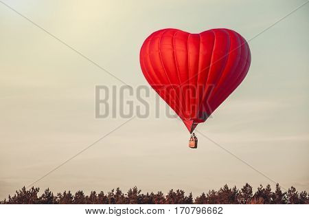 Beautiful red air balloon in the shape of heart fly high in sky. Romantic date present trip on Valentine's Day. Sports and recreation travel postcard. Nature background. Vintage retro toning effect
