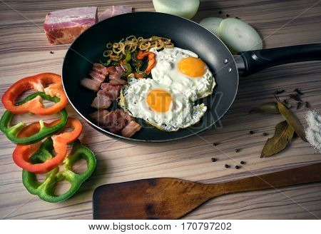 fresh fried eggs with vegetables and bacon were photographed in studio