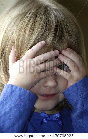 Little girl playing peekaboo peek-a-boo game