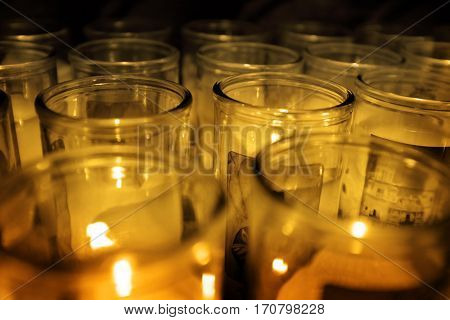 Glass jars candles glowing in the darkness for light