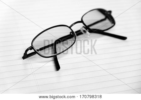Black frame glasses on notebook for business or studying