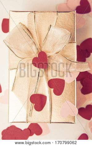 Overhead shot of a gold gift box tied with ribbon to a bow and scattered with red and pink confetti love hearts.