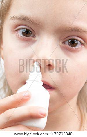 girl with flu using nose spray. A close up