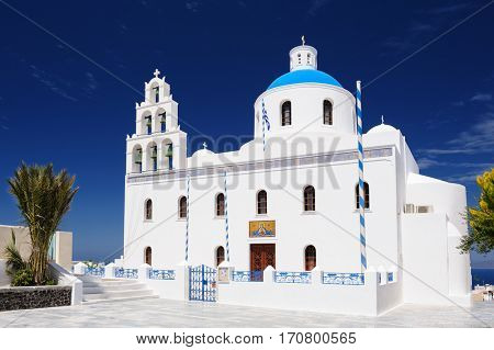 Oia, Santorini island, Cyclades, Greece - April 23, 2016: View to Orthodox church of Panagia with bell tower at central square. Oia is a small town and former community in the South Aegean on the