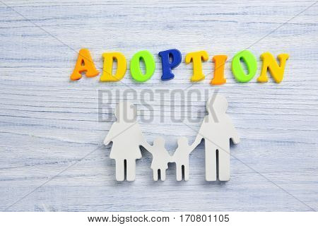 Word ADOPTION and figure in shape of family on light wooden background