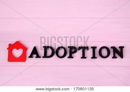 Word ADOPTION and figure in shape of house on wooden background