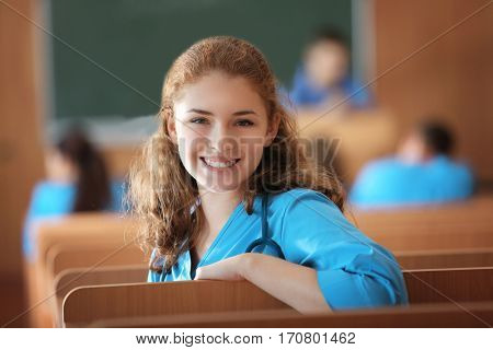 Young female student at lecture indoors