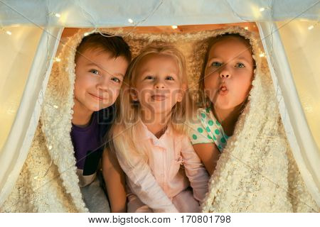 Cute little children playing in hovel at home