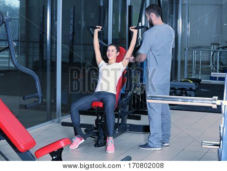 Rehabilitation concept. Young woman doing exercises under physiotherapist supervision