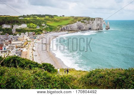 Fantastic white sand beach and cliffs of Etretat, norman french town outdoor landscape. View above the town and the bay of Falaise d'Amont Etretat City, famous landmark of Normandy in France, Europe