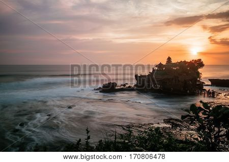 Tender sea view sunset near famous tourist landmark of Bali island - Tanah Lot temple. Long exposure technique for frozen water effect. Tropical nature landscape of Indonesia, Asia