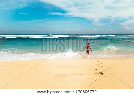 Young fit woman going to swim in colorful sea with sunny blue sky on horizon at Bali island, Indonesia. Outdoor nature landscape of ocean waves and clear white sand beach in Southeast Asia. poster