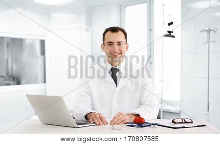 Doctor sitting at table in consulting room