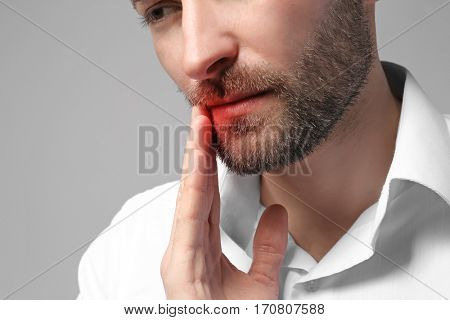 Man suffering from tooth pain on gray background. Health care concept