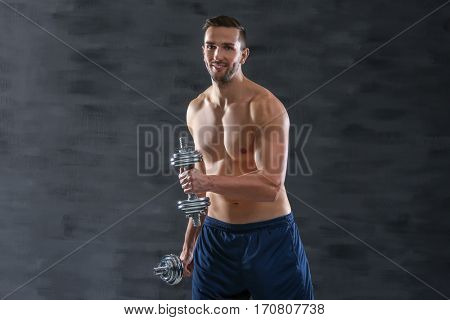 Sporty man doing exercises with dumbbells on dark background