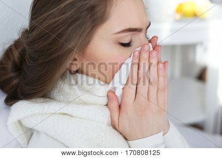 Young ill woman with tissue at home, closeup