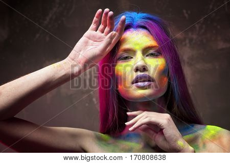 Portrait of beautiful young woman with amazing body-art on grey textured background