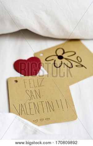 closeup of a brown paper note with the text feliz san valentin, happy valentines day written in Spanish and a flower drawn in another note, and a red heart, on the white sheets of an undone bed