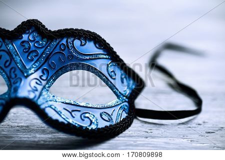 closeup of an elegant blue and black carnival mask on a rustic wooden surface
