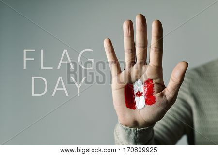 the text Flag Day and the flag of Canada painted in the palm of a young caucasian man