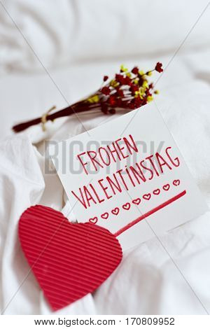 closeup of a red heart, a white paper note with the text frohen valentinstag, happy valentines day written in german, and a bunch of dry flowers on the white sheets of an undone bed