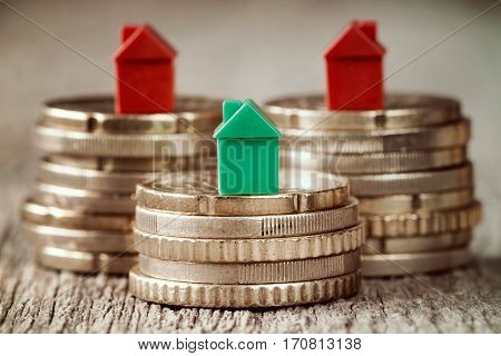 Miniature houses resting on coins stacks. Concept for property ladder mortgage and real estate investment