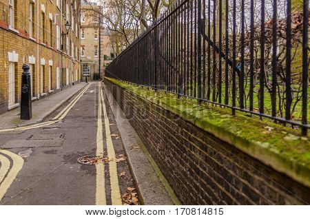 narrow street in the old style only for pedestrians with a green low wall of the park metal fence brick buildings street with yellow painted lines