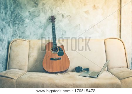 Guitar with laptop and headphone on a sofa. Vintage tone.