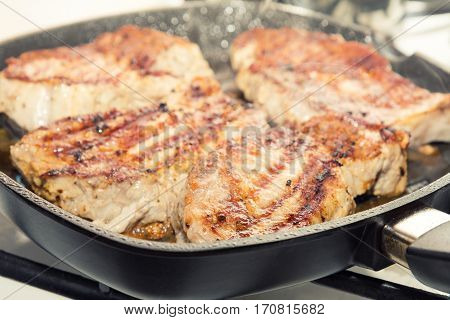 Fresh Pork Steak Cooking On Pan Grill.