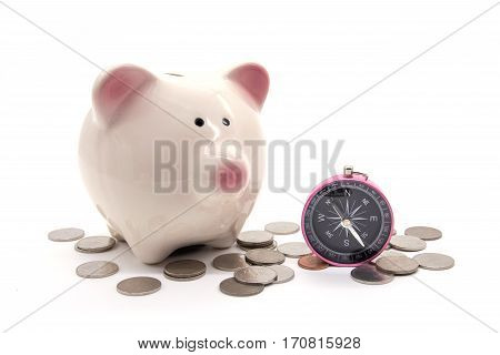 piggy bank with compass and coin on white background